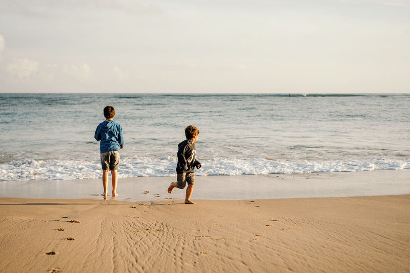 Full length of children on beach against sky