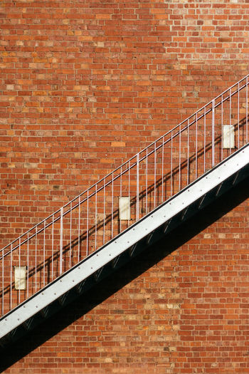 Low angle view of staircase against brick wall