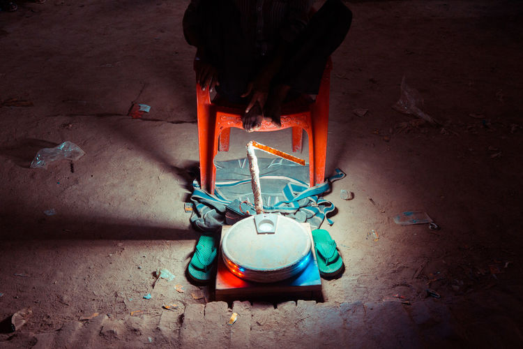 Low section of man sitting by weight scale on footpath at night