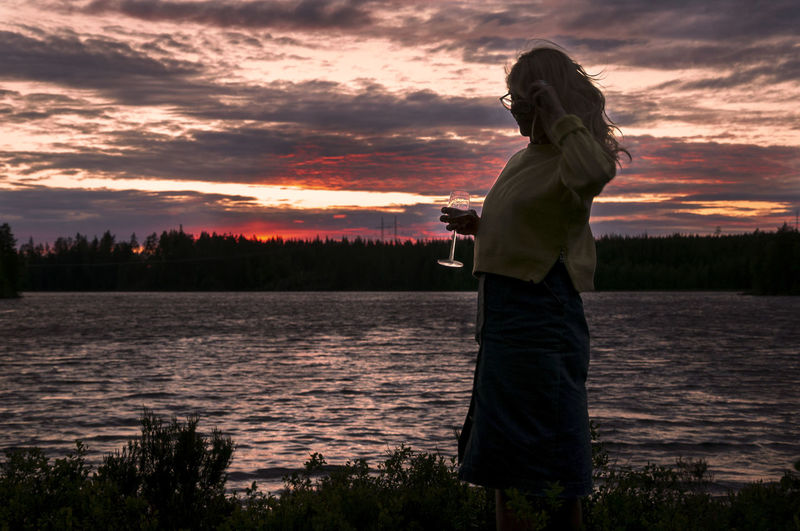 Side View Of Mature Woman Holding Wineglass While Standing By Lake Against Sky During Sunset