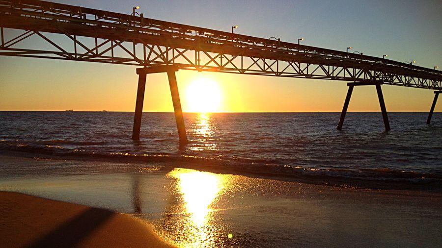 Silhouette of bridge over sea during sunset