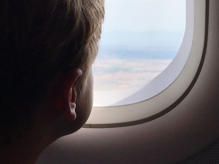 Close-up of boy looking through airplane window