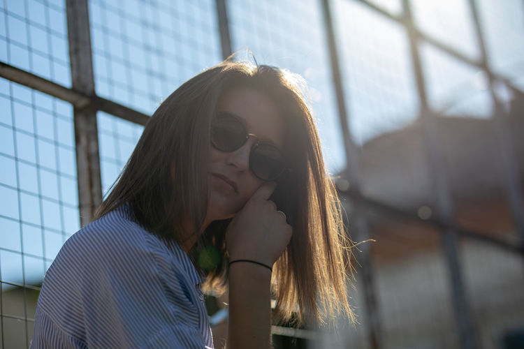 Portrait of young woman wearing sunglasses against metal grates