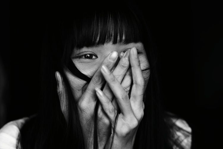 Close-up of happy young woman covering mouth while looking away against black background