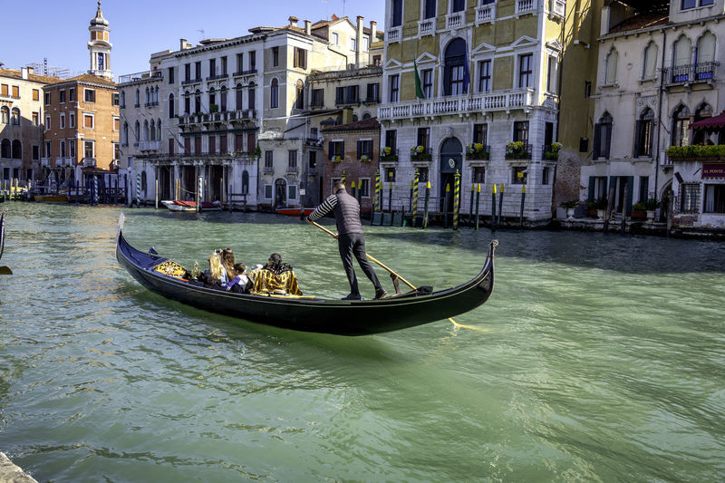 People in boat on canal in city