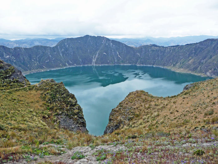Scenic view of quilotoa volcanic crater lake and mountains against sky