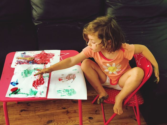 High angle view of cute girl painting on paper