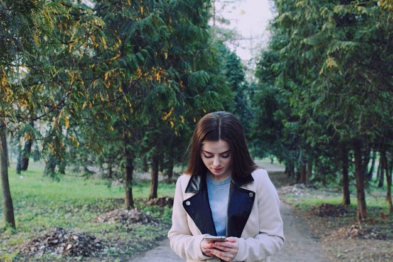 Young woman using phone in forest
