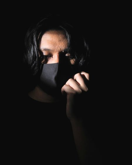 Close-up portrait of woman covering face against black background