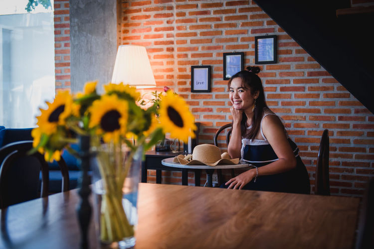 Young woman sitting on table at cafe