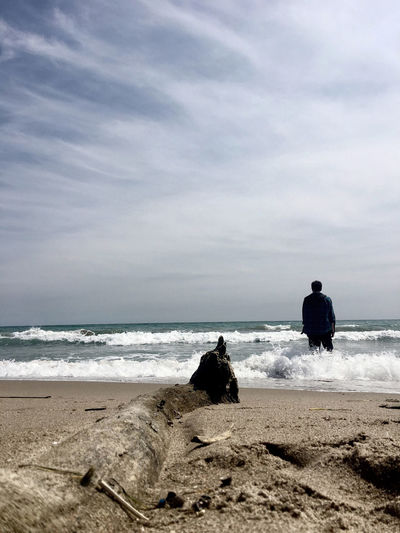 Rear view of man standing on shore at beach against sky