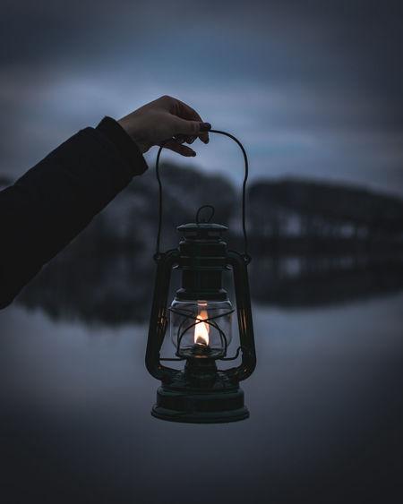 Close-up of woman holding illuminated lantern against sky at dusk