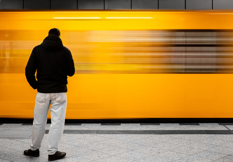 Rear view of person standing by moving train