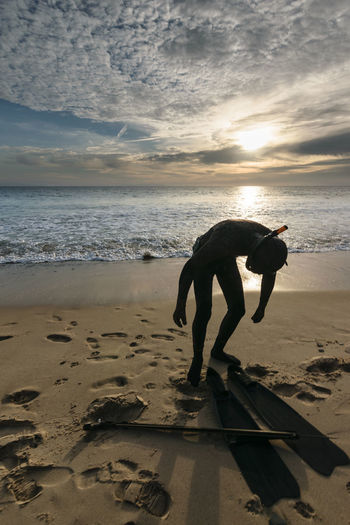 A snorkeler with a harpoon standing on a beach at sunset and clouds in the sky in Tarifa, Spain- Cloud - Sky Diver Fisherman Harpoon Horizon Over Water Hunter Leisure Activity Lifestyles Sand SCUBA Silhouette Snorkel Snorkeling Spear Water Watersports
