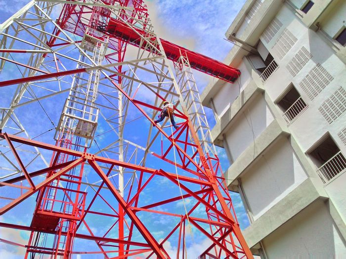 Low Angle View Of Man Climbing On Communications Tower