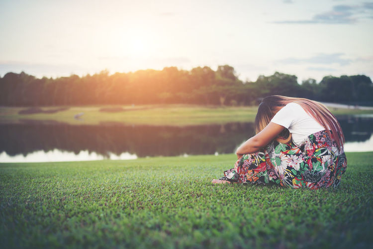 Depressed Woman Sitting On Field During Sunset