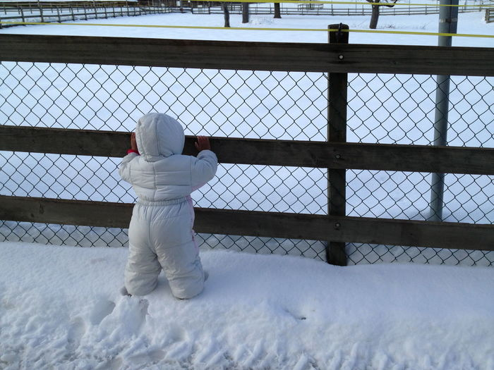 Rear view of child wearing warm clothing standing by fence