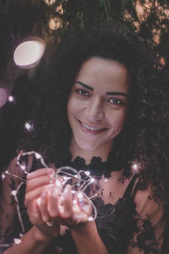 Close-Up Portrait Of Beautiful Woman Holding Illuminated Lights