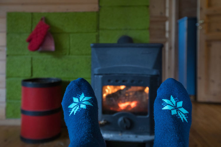Relaxing in front of the fireplace after a long winter hike Human Body Part Blue One Person Low Section Body Part Real People Wood - Material Unrecognizable Person Flame Human Foot Burning Warm Clothing Fireplace Fire - Natural Phenomenon Wellbeing Relaxation Cosy Home Interior Sock Winter Comfortable Heat - Temperature Snowflake Lifestyles Indoors