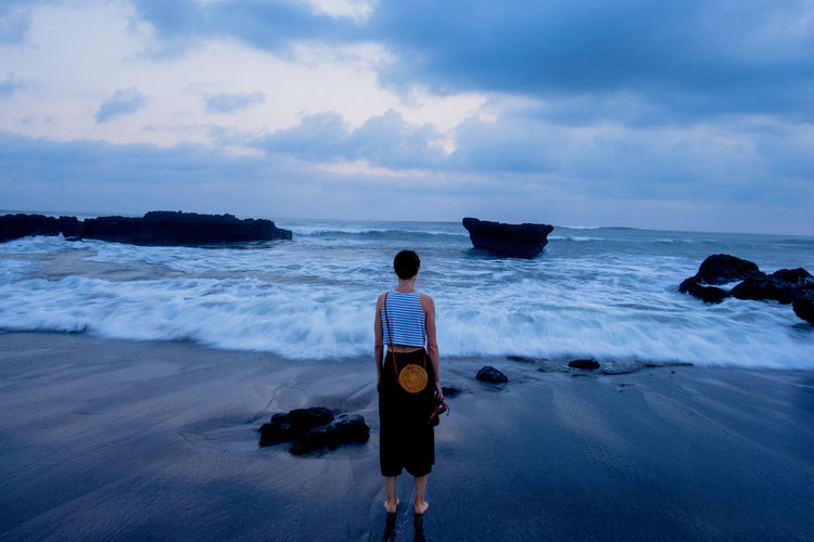 A woman stands at a beach, next to the crushing waves. Woman Beach Beauty In Nature Cloud - Sky Horizon Over Water Land Leisure Activity Lifestyles Looking At View Motion Nature Outdoors Real People Rear View Scenics - Nature Sea Sky Standing Water Wave
