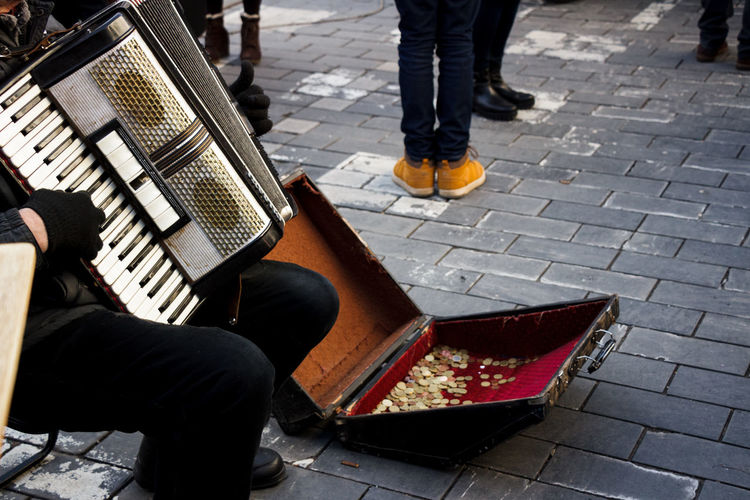 Low section of male street musician playing accordion on footpath