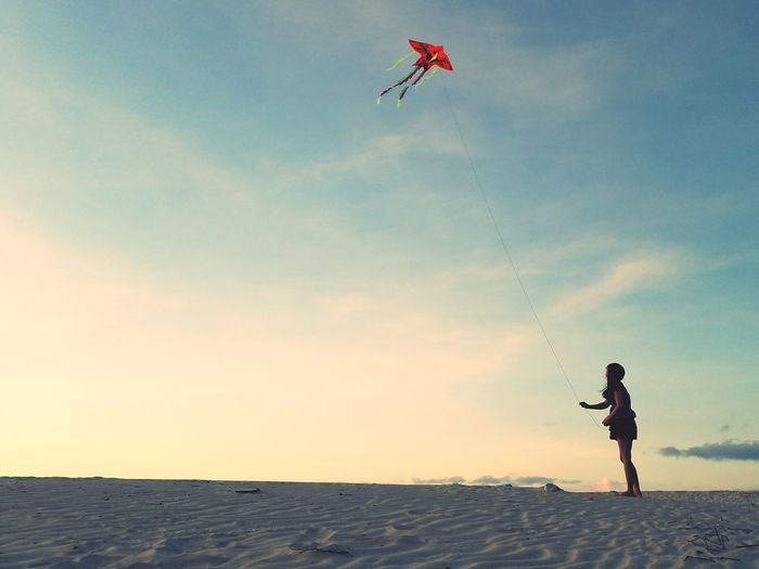Woman flying kite at beach against sky