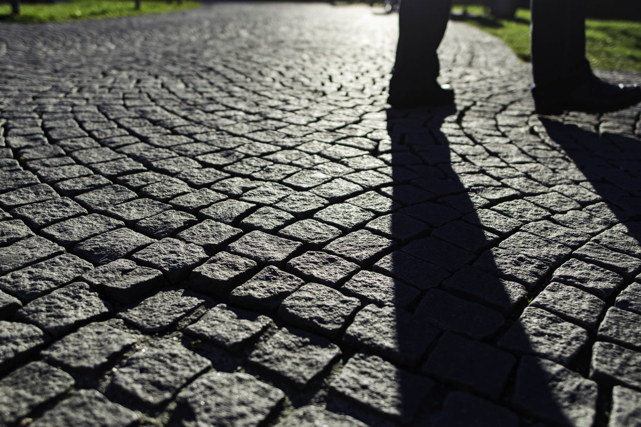 low section, sunlight, human leg, cobblestone, real people, day, shadow, one person, outdoors, human body part, childhood, close-up, people