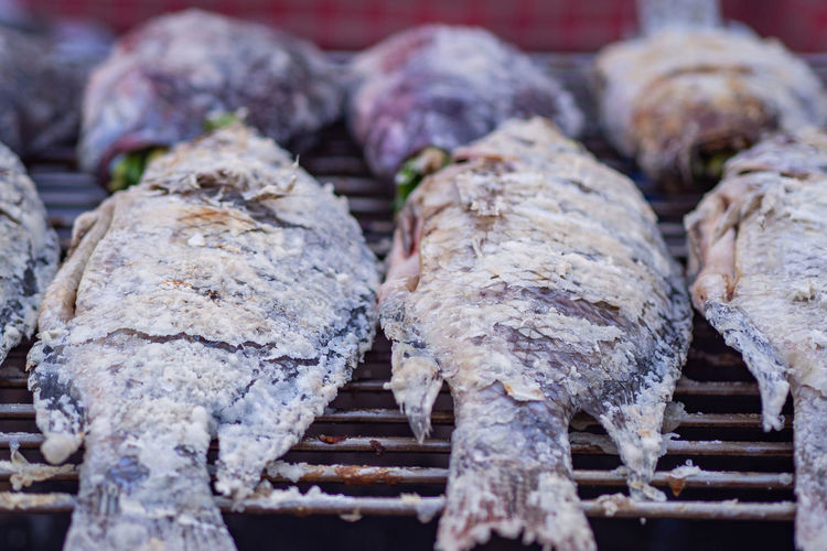 Close-up of tilapia grilled and sprinkled with salt on the grill.