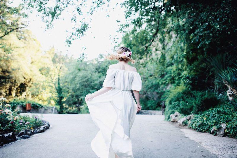 Rear view of woman walking by plants