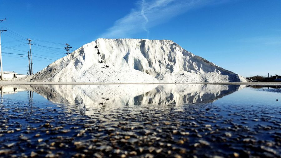 Surface Level Of Salt Heap By Puddle Against Sky