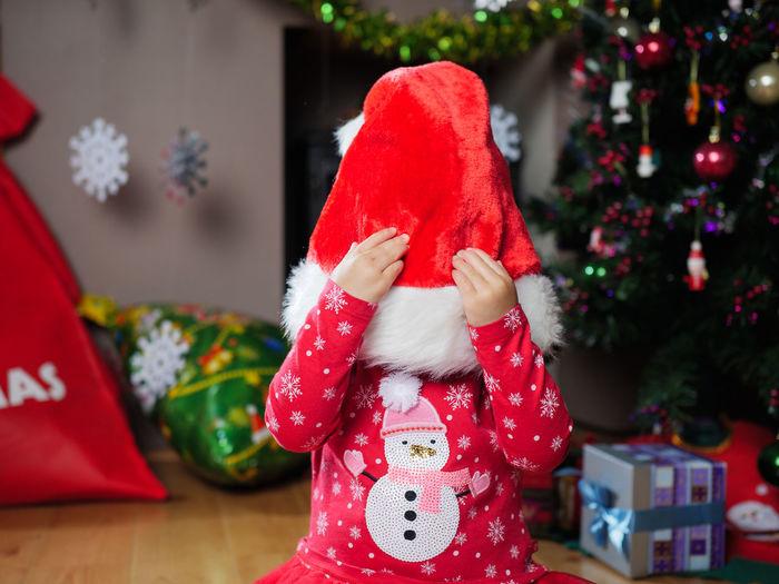 Close-up of baby girl wearing santa hat at home