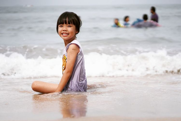 Asian girl having summer holiday ar beach EyeEm Selects Water Child Wave Sea Childhood Smiling Beach Portrait Sand Happiness Beach Holiday Children Sunbathing Swimwear The Portraitist - 2018 EyeEm Awards