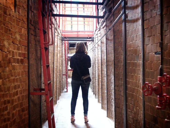 Rear view of woman standing in corridor