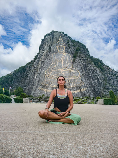 Portrait of woman meditating in front of mountain against sky