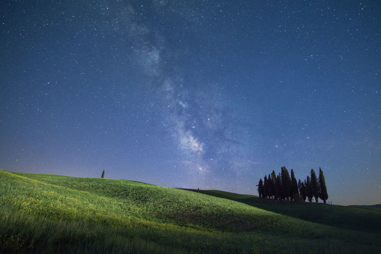 Scenic View Of Green Landscape Against Star Field At Night