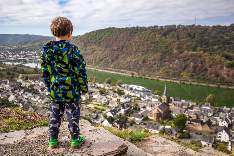 Rear view of boy standing on cliff by house and river in town