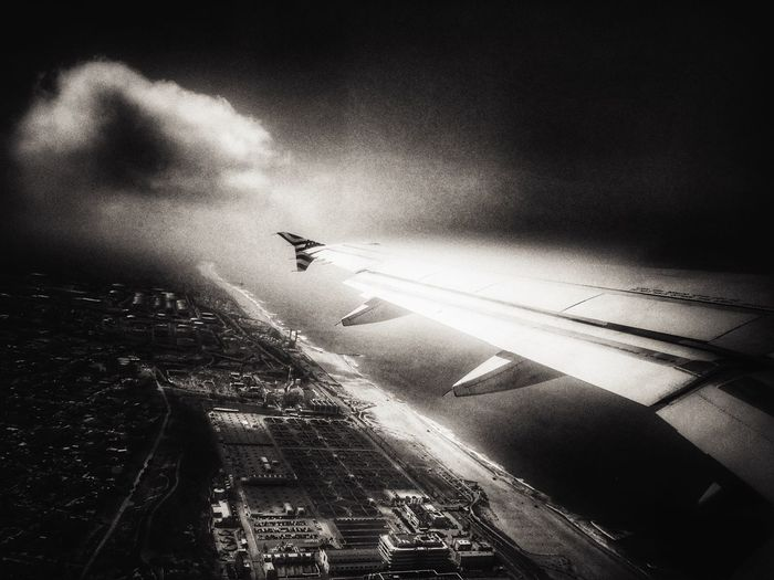 High angle view of airplane flying in city