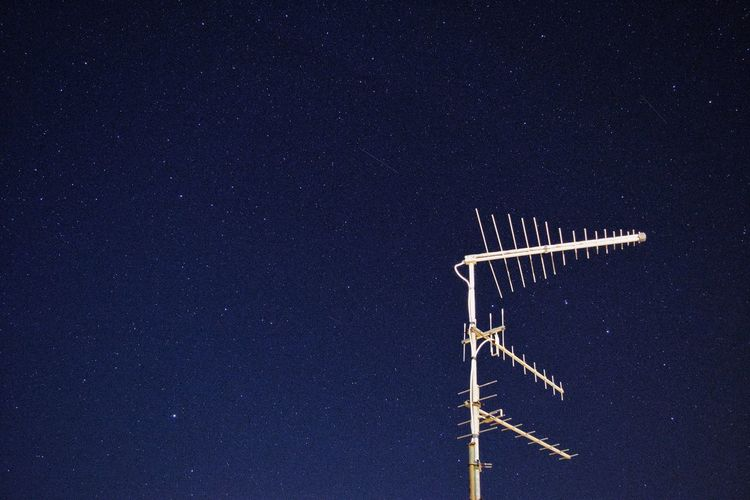Low angle view of aerial against clear sky at night
