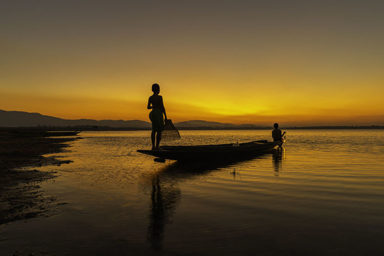 Silhouette men on boat in sea against sky during sunset