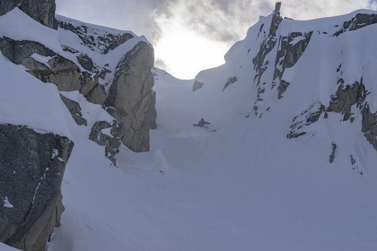 Ski Skier Skiing Winter Snow Cold Temperature Mountain Mountain Range Steep Extreme Sports Lone Solo Chute Couloir Sky Powder Slope Terrain Rugged Remote Wild Dangerous Athlete Skill  Speed