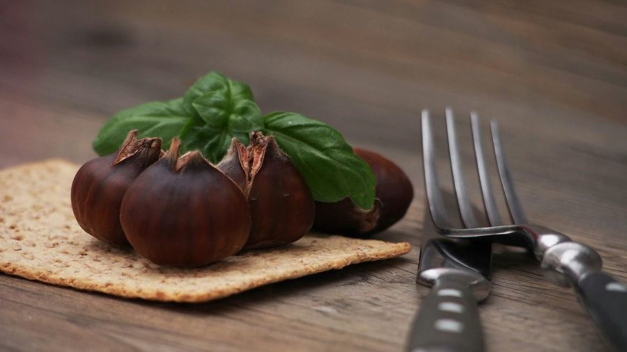 Close-up of fig with cookie and cutlery on table