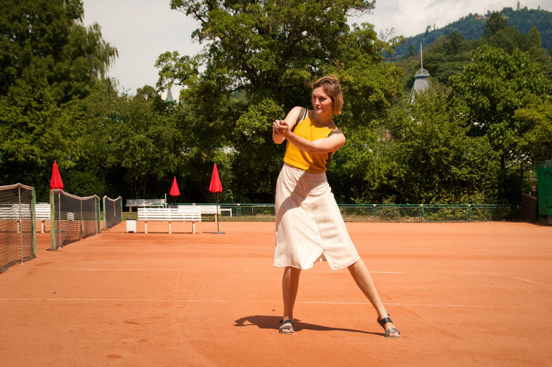 Full length of woman standing at tennis court