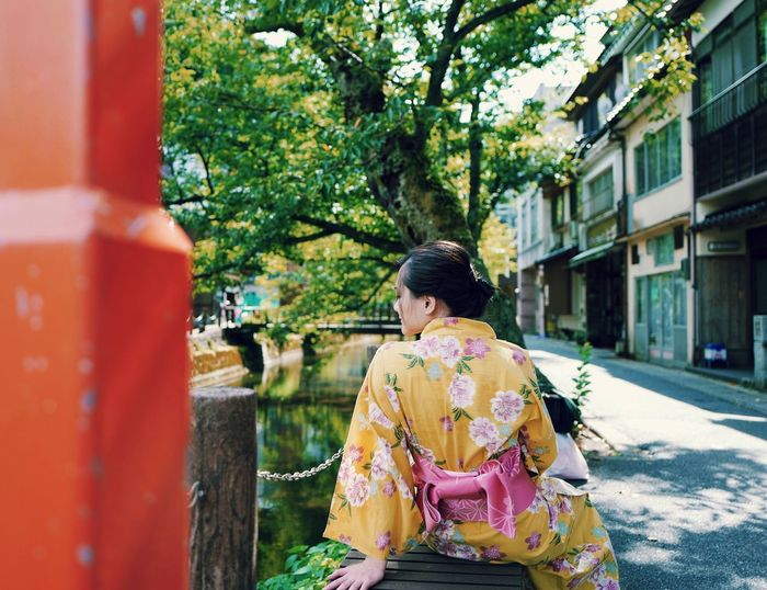 Japan Adult Architecture Building Exterior Casual Clothing City Day Floral Pattern Hair Hairstyle Kimono One Person Outdoors Plant Real People Rear View Sitting Tree Waist Up Women Young Adult