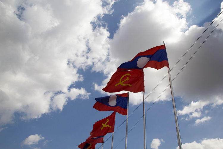 Cloud - Sky Sky Low Angle View Environment Flag Patriotism Nature No People Pole Day Wind Red Outdoors Multi Colored Blue Textile Lao Flag Lao Revolution Party Flag Bacground Communist