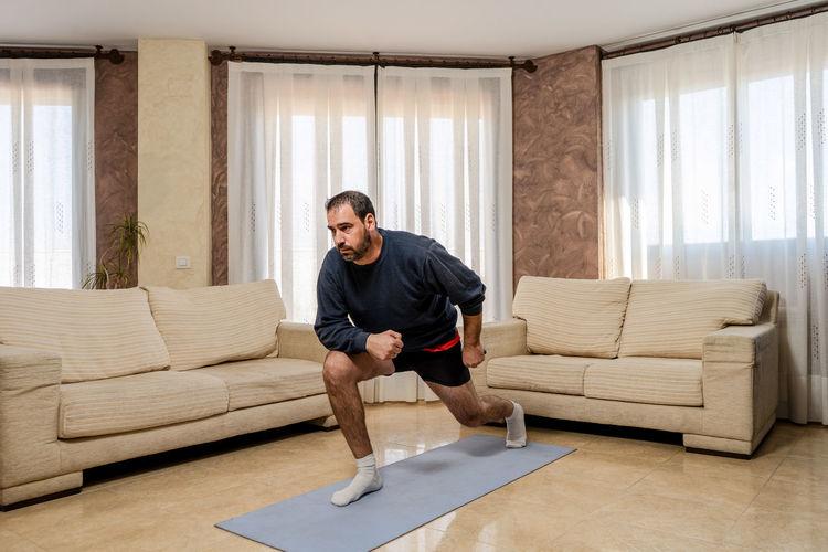 Full length of man sitting on sofa