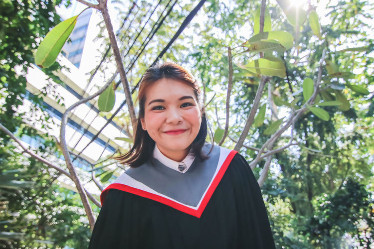 Portrait Of Smiling Young Woman Wearing Graduation Gown Against Tree