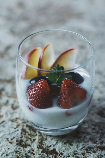 Close-up of strawberries and apple in yogurt on table