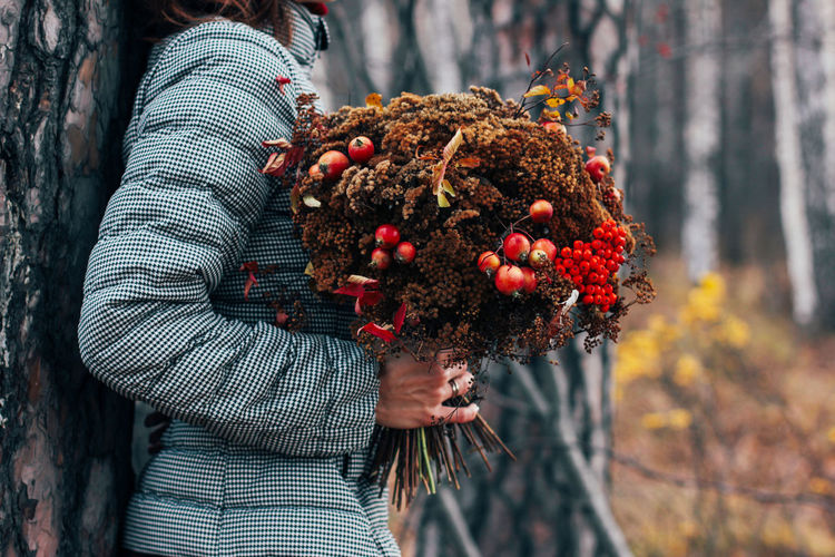 Close-up of woman holding strawberry plant against tree trunk