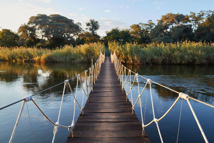 Wooden bridge over lake against sky