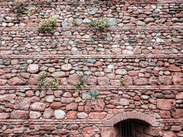 Red stone wall History Historic Fortress Fort Fortress Wall Castle Castle Walls Boulders Layers Stripes Window SPAIN Red Stone Backgrounds Full Frame Pattern Textured  Close-up Architecture Built Structure Creeper Growing Creeper Plant Worn Out Wall Weathered Peeled Decline Young Plant